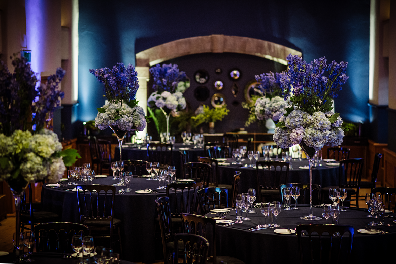 tables set with glasses and large bunches of flowers