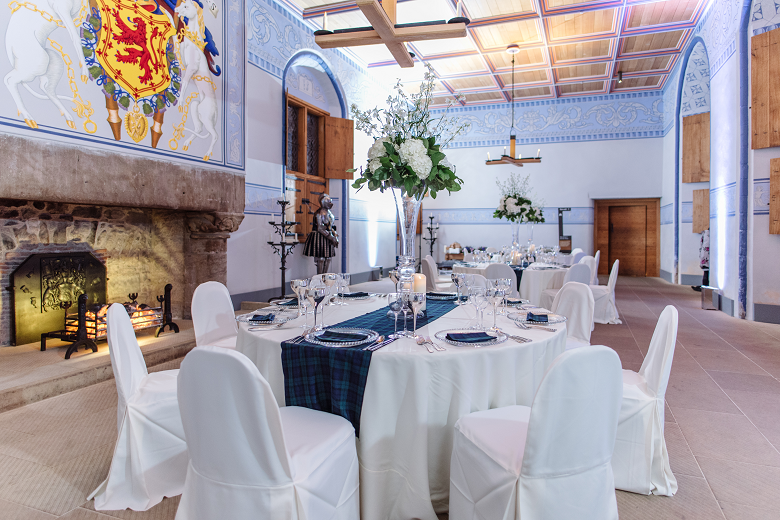 table and chairs covered in white cloth, set for a formal meal