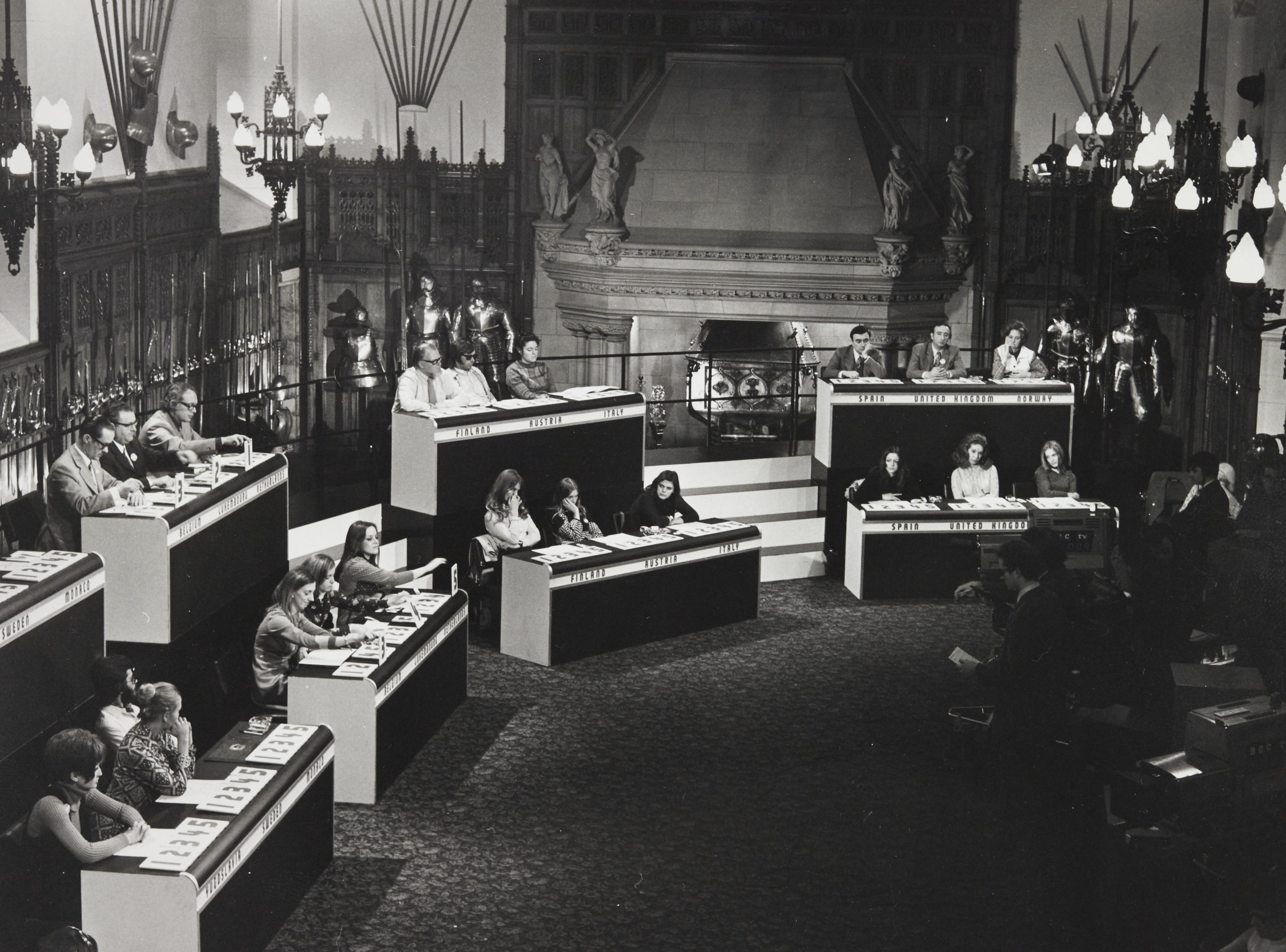 rows of desks with three people at each in a room with suits of armour at the back