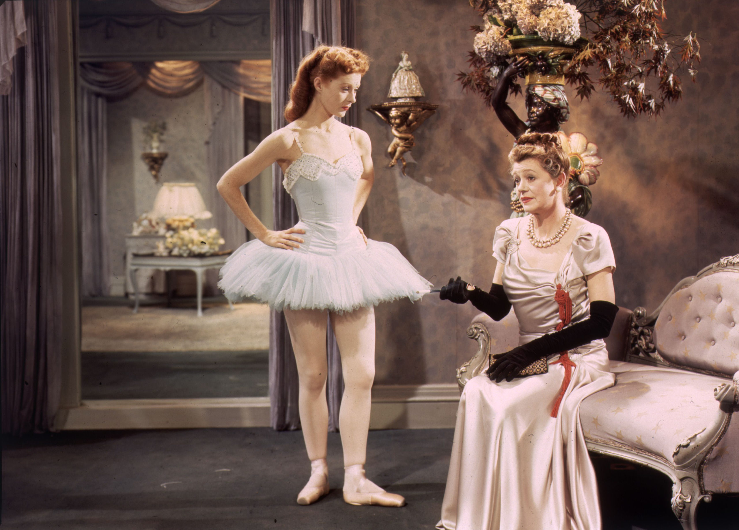 ballet dancer with hands on hips looks at seated woman in formal gown