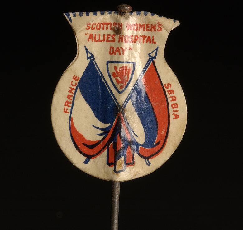 A thistle-shaped flag on a small pole with a design featuring the intertwined flags of France and Serbia and the slogans for Scottish Women's Hospitals Day