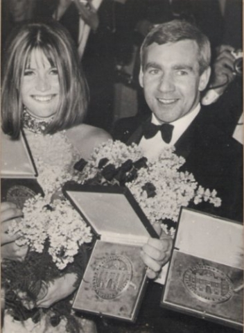 woman and man smiling and holding flowers and medals