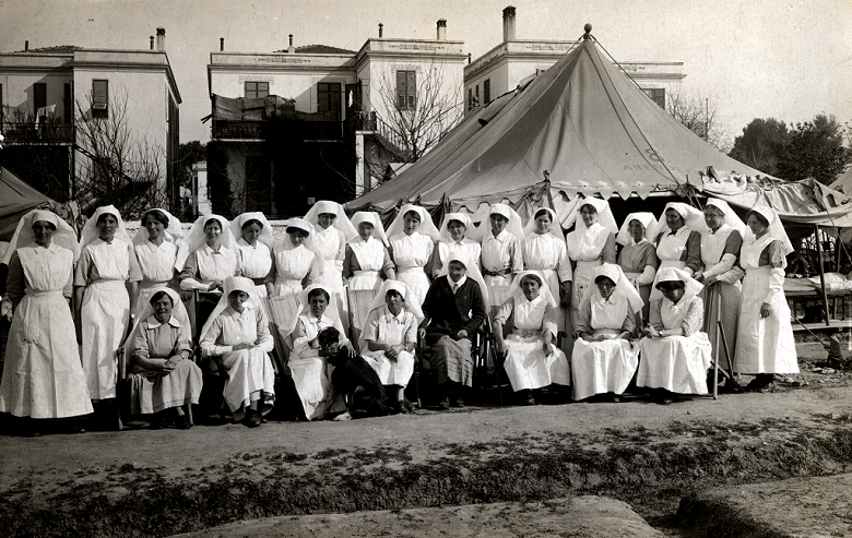 A group of nurses in uniform pose for a group photo in front of a hospital tent