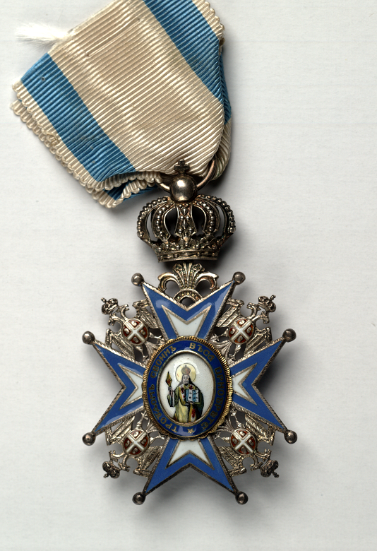 A close-up photo of a medal featuring an image of a saint on a blue and white background
