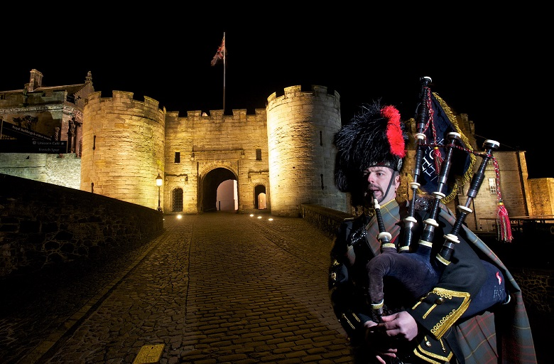 man playing bagpipes in front of a castle
