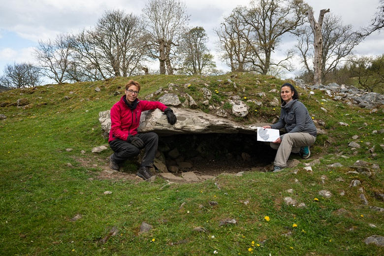 two women sit either side of the entrance to a burial cairn.