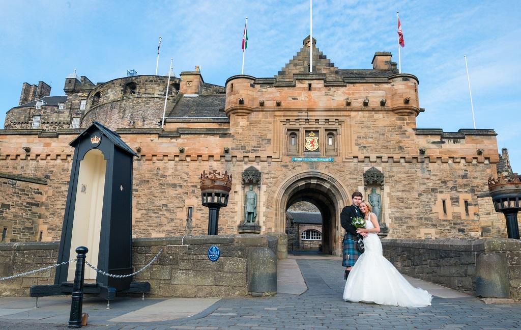 couple standing outside a castle
