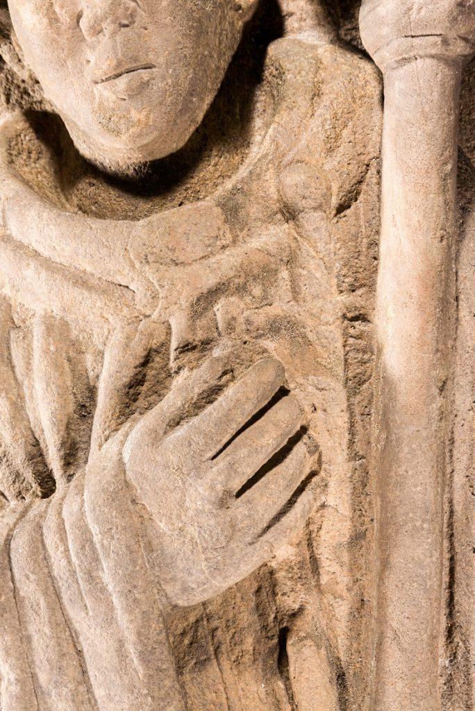 close up of the carving showing the detail of the carved hand and dagger