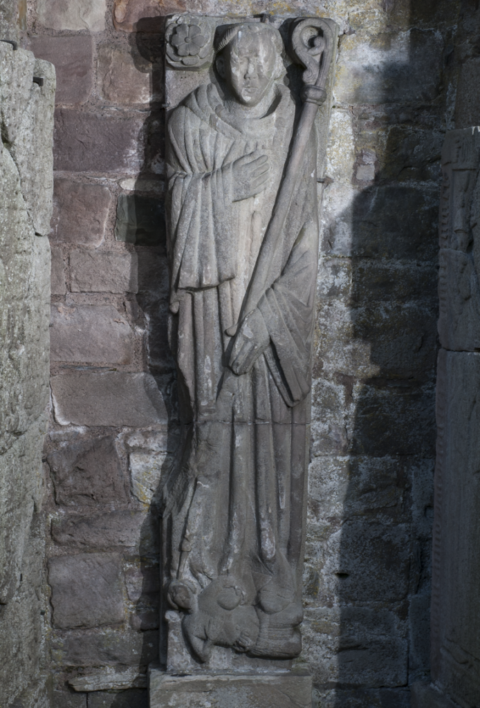 head to toe view of a carved monastic figure