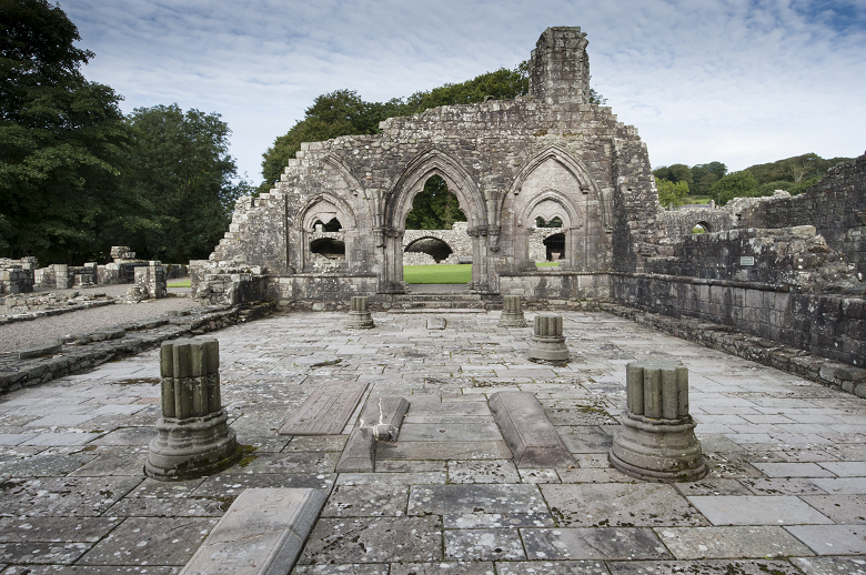 The ruined chapterhouse at Dundrennan Abbey. The feet of pillars and some walls remain.