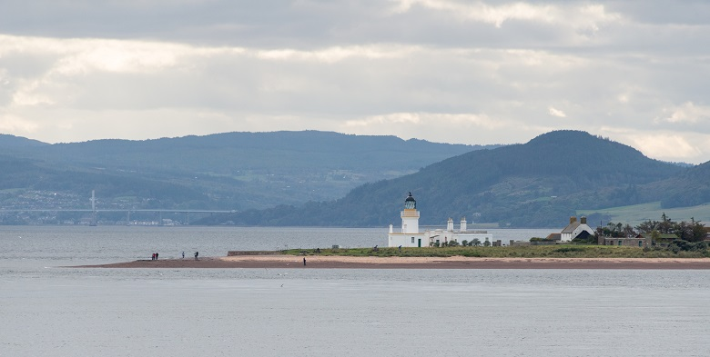 A white lighthouse on a promontory with mountains and the faint outline of a bridge in the background