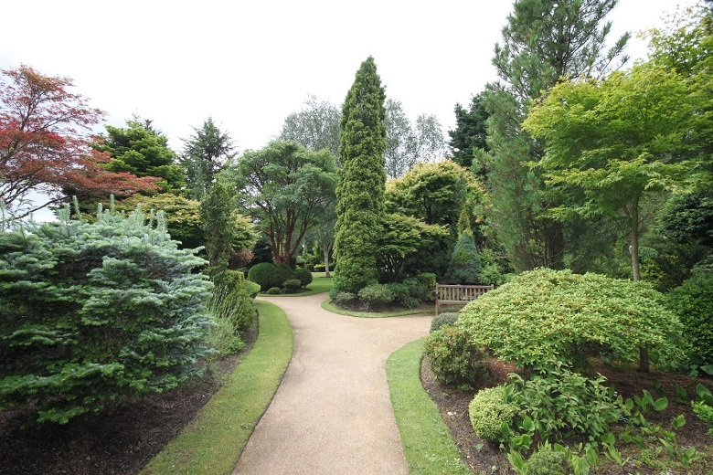 A path leading past flower beds and shrubs in a walled garden