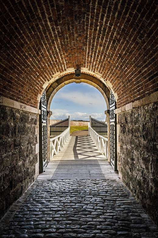The entrance to a military fort through a stone archway and over a bridge
