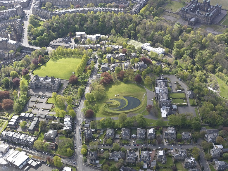 An aerial view of an urban green space, artistically laid out using grass and water at varying levels