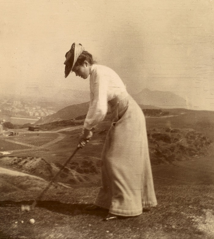 An early photograph of a woman playing golf with the hills of Edinburgh in the background