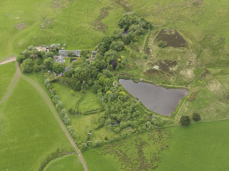 An aerial view of a small rural farm surrounded by trees and a small triangular loch