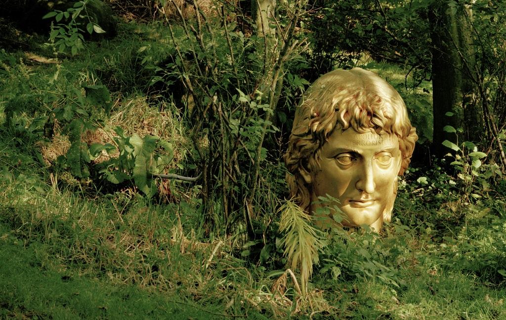 A sculpture of a golden head in a garden