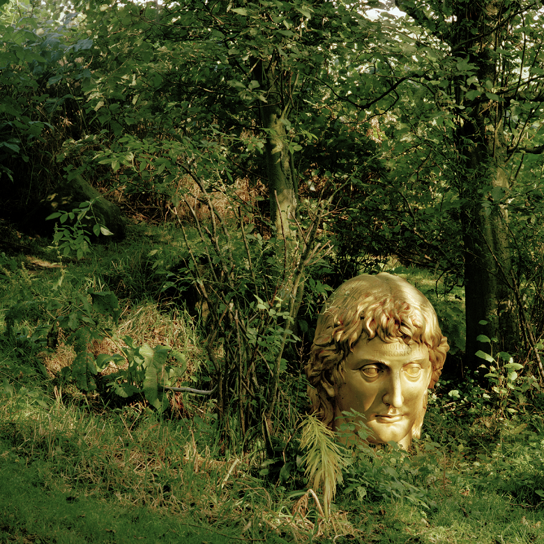 A large gold sculpture depicting the head and face of a man surrounded by trees and grass in garden