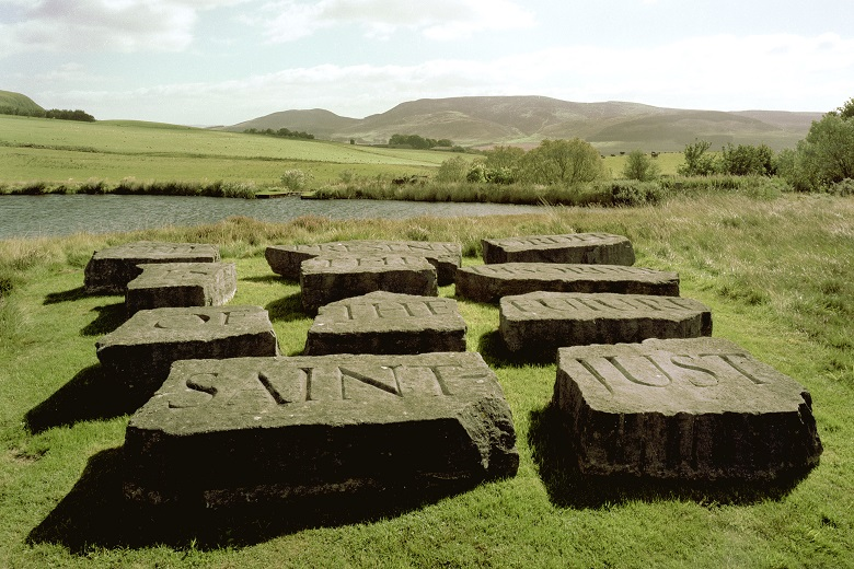 Nine inscribed stones arranged as a sculpture beside a small loch