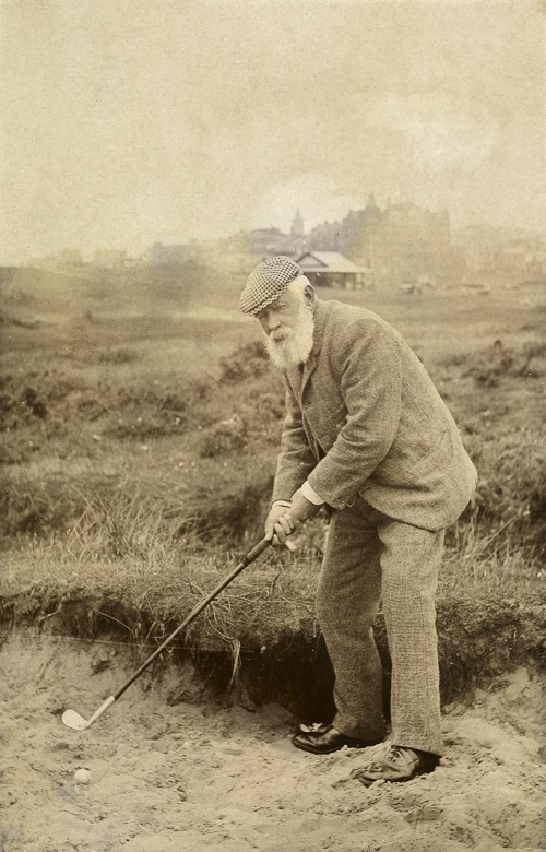 An archive photo of Old Tom Morris preparing to take a shot while playing golf