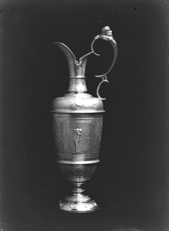 A trophy in the form of a silver claret jug with a golfer engraved on it