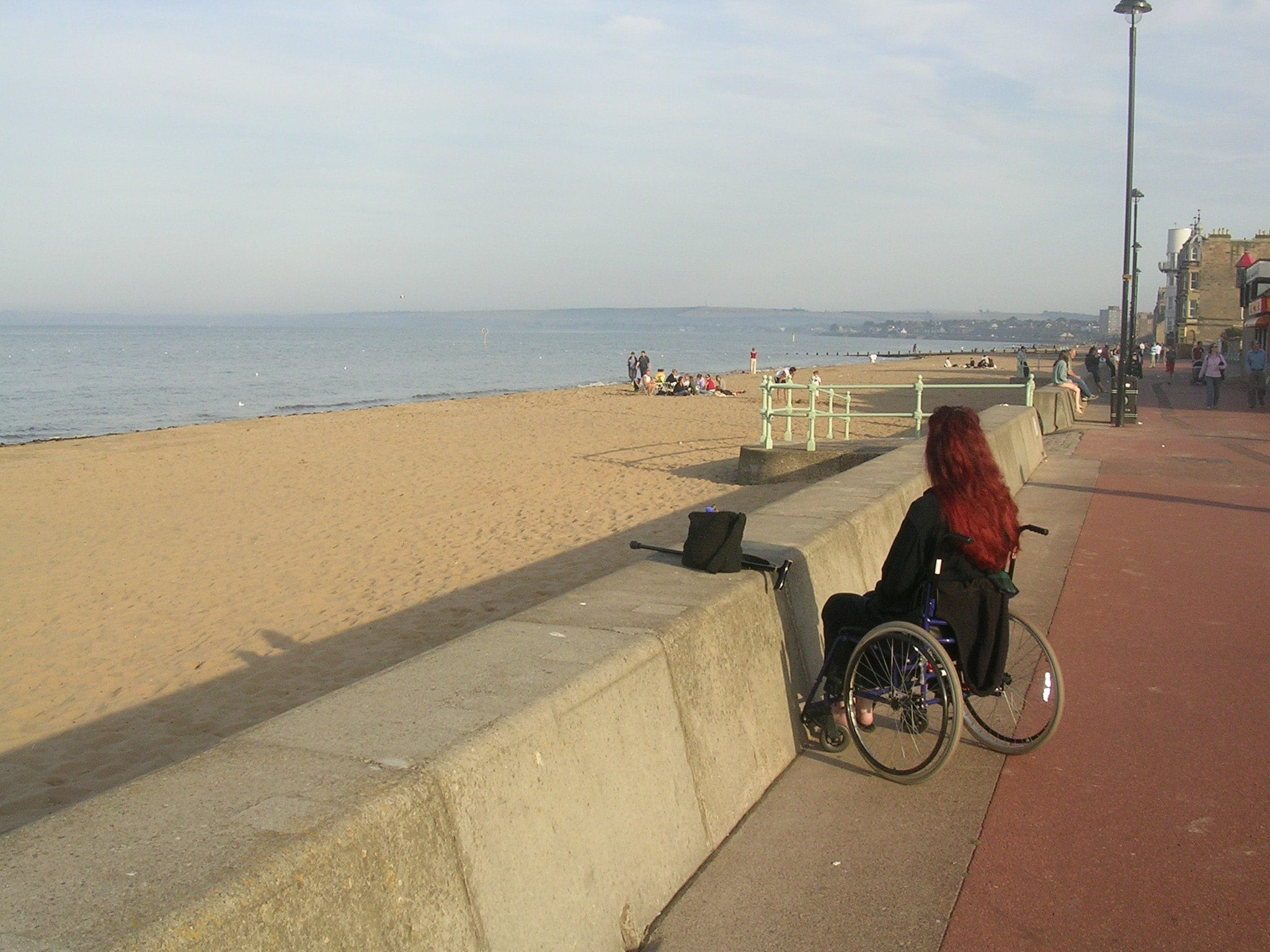 A person in a wheelchair looks out to sea from an urban promenade. There is a beach between the promenade and the water but no access path can be seen
