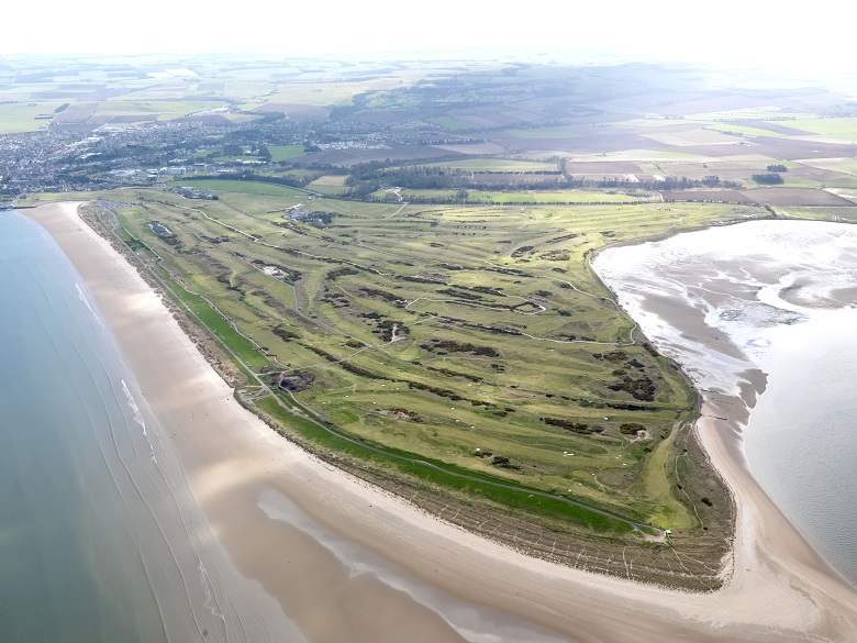 An aerial photo showing several links golf courses surrounded by beaches and the sea