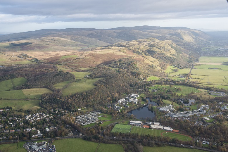 An aerial view of modern university buildings set into green fields and countryside with mountains in the background