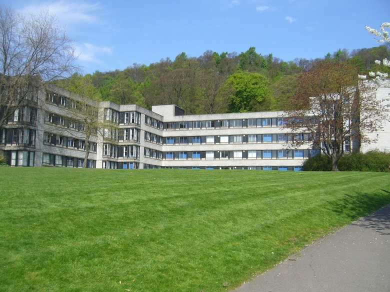 Grass in front of a 1960s university building, with a tree-covered hill in the background