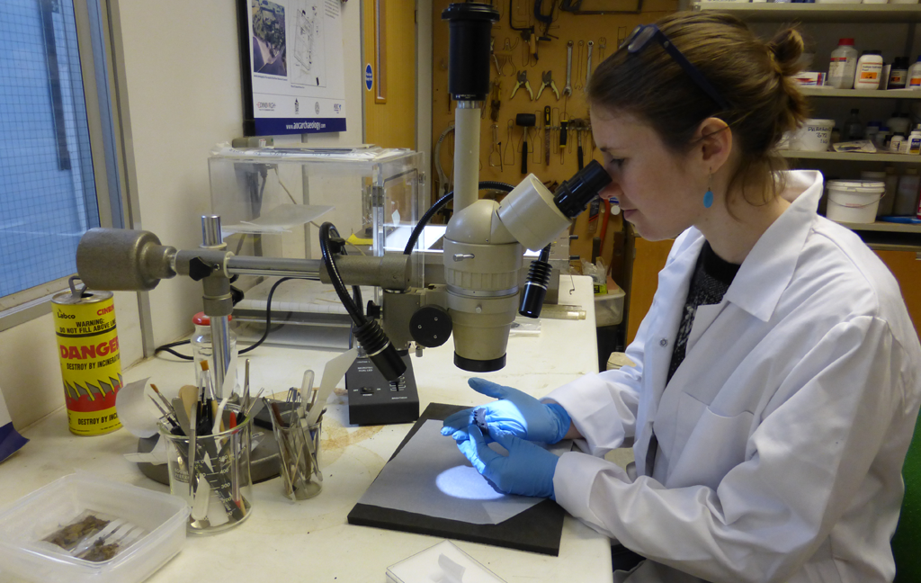 person in lab coat and protective gloves inspecting something under a microscope