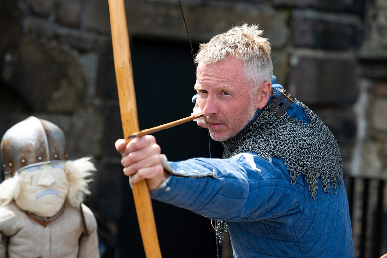A living history performer takes aim with a longbow