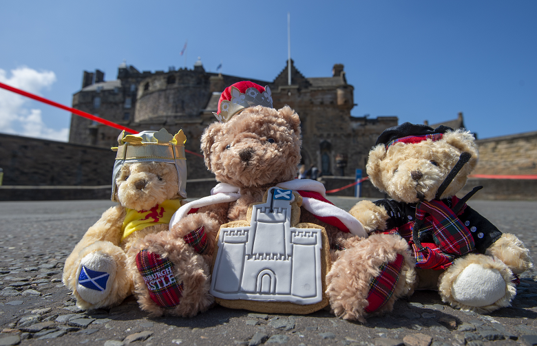 Three soft toy teddy bears photographed in front of Edinburgh Castle