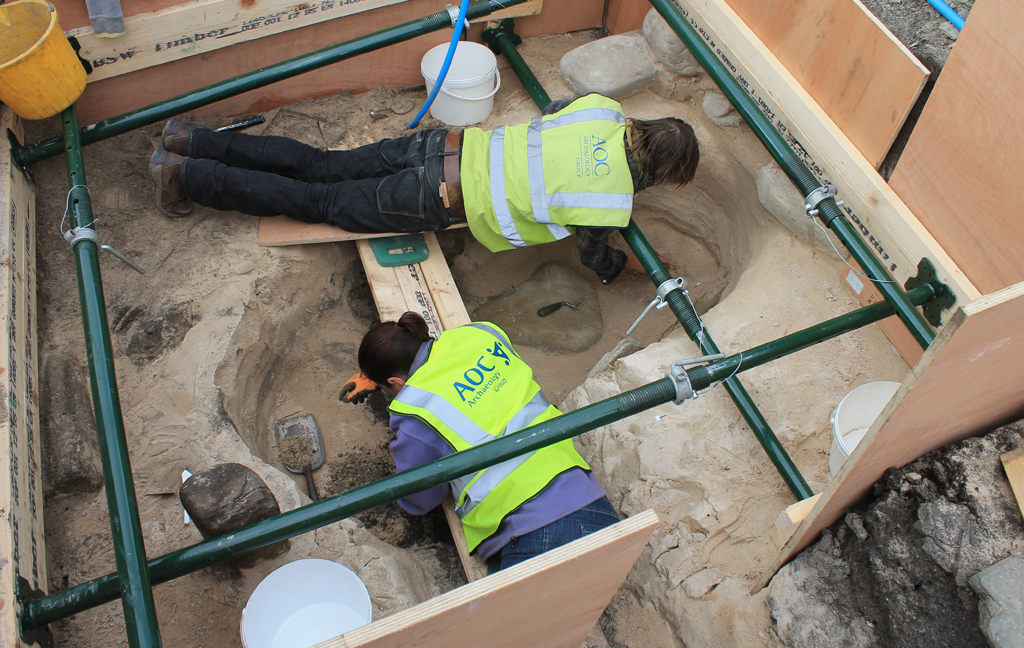 two people lying on scaffold looking into a trench