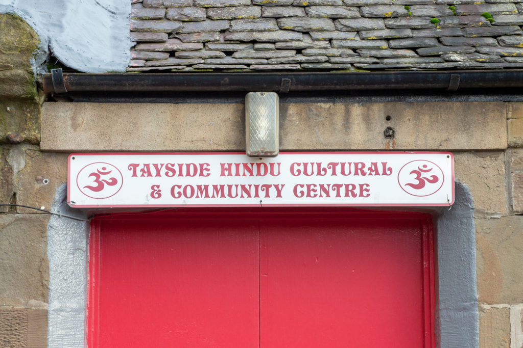 A sign above the Hindu Cultural and Community Centre with two symbols on either side of the centre's name