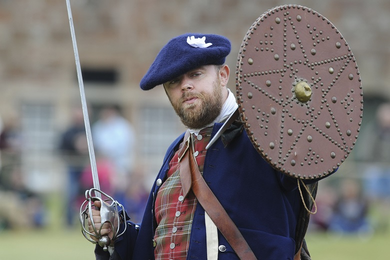 A living history performer wielding a sword and a shield
