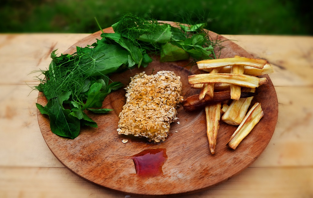 A medieval take on fish and chips presented on a round wooden board with green leaves and red sauce