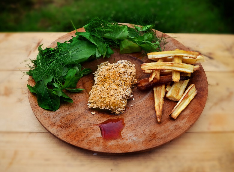 A medieval take on fish and chips presented on a round wooden board with green leaves and red sauce, one of the dishes used in the Taste the Truth round in a a panel show called Historic Fact or Fake News
