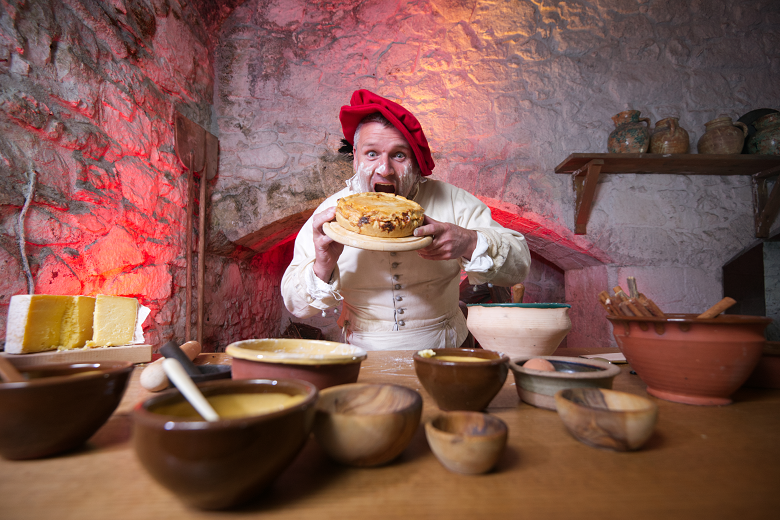 A living history performer tucks into a large meat pie in a recreation of a medieval castle kitchen