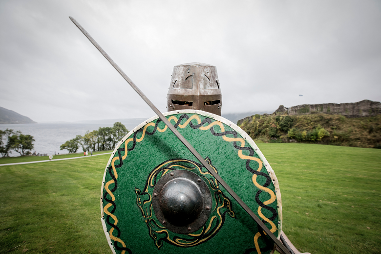 A living history performer wearing a metal helmet and holding a long sword and a round, green shield