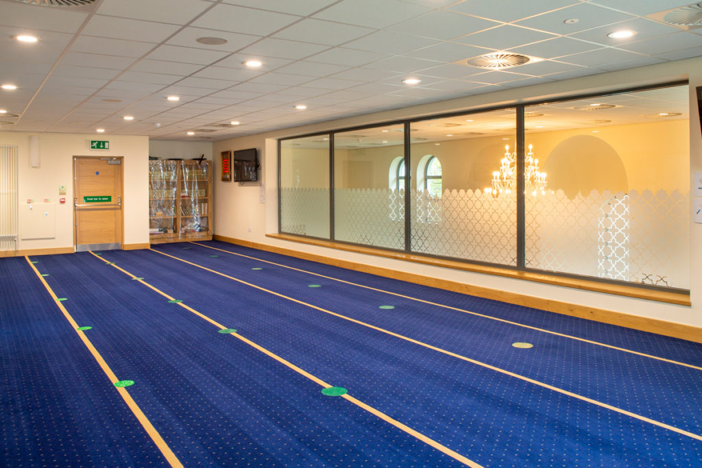 A prayer room with a wall of windows and carpet with lines running lengthways
