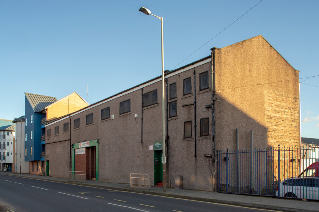 A low, industrial style building with small windows and a doorway reading Jame Masjid Bilal