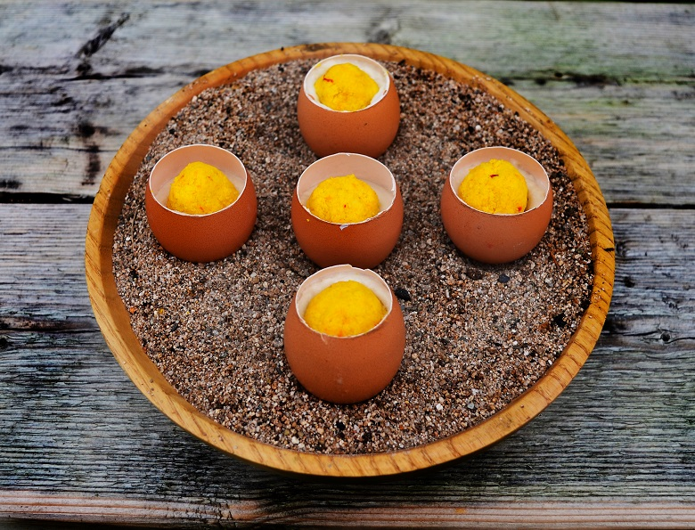 5 eggshells filled with sweet ingredients arranged in a cross shape on a round wooden plate