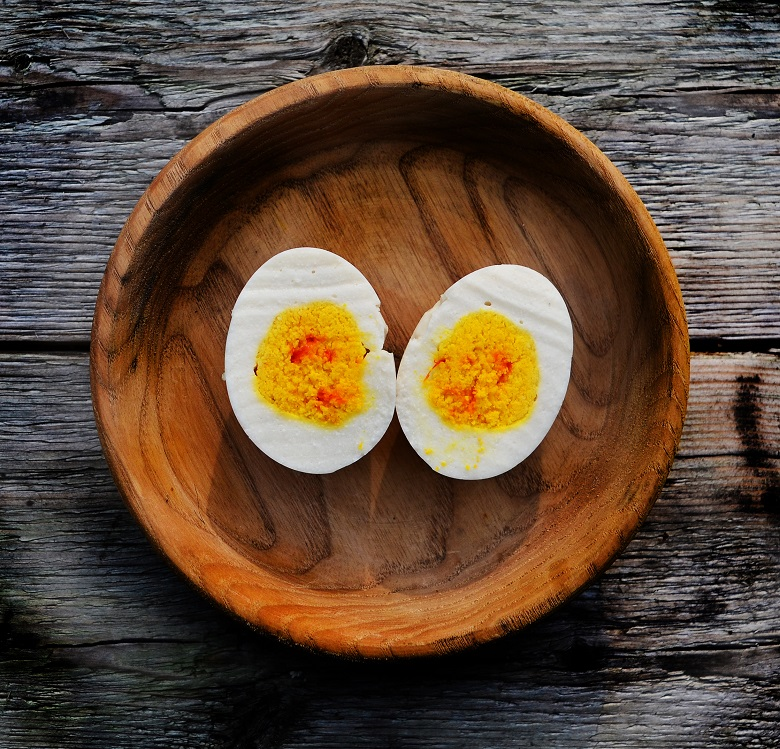 """What appears to be a halved boiled egg served in a wooden bowl - on closer inspection the """"egg"""" has been recreated using other, sweet ingredients"""