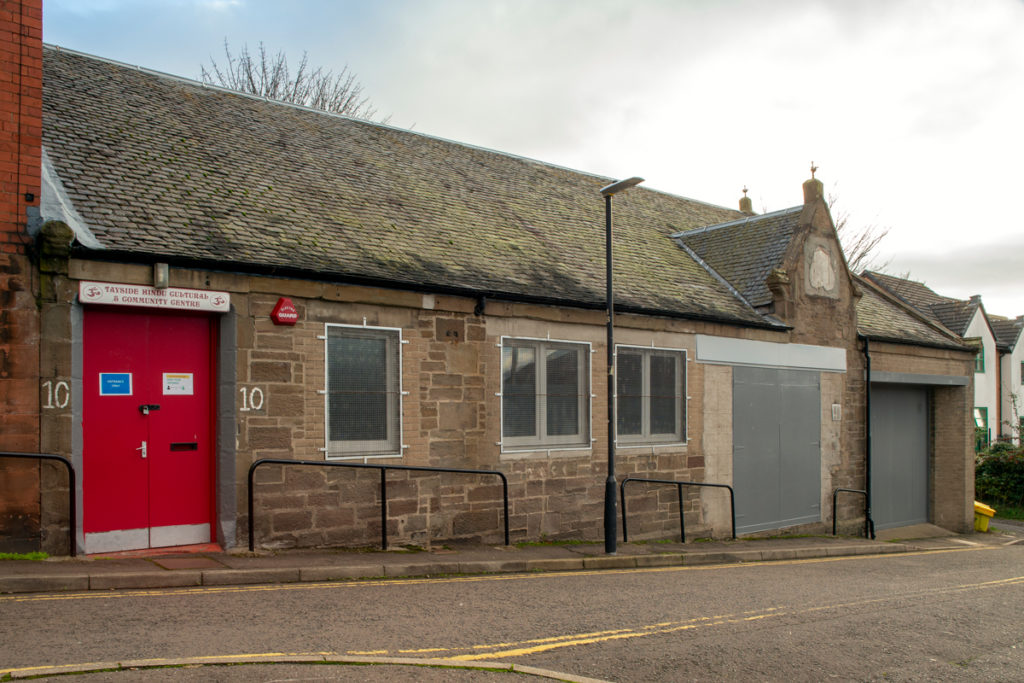 A low, unassuming building with a red door