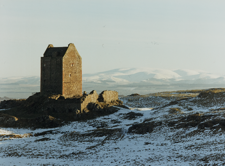 A light covering of snow on the hillside in front of the remains of a stone tower house