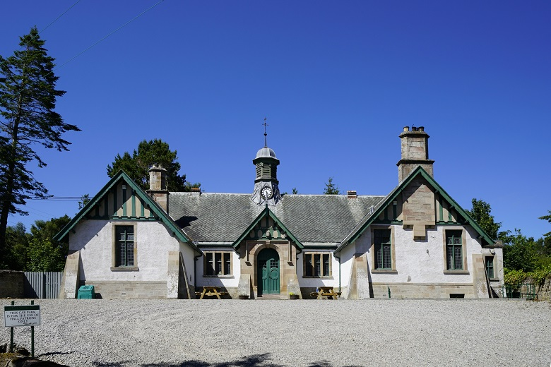 A Carnegie funded, one-storey rural village hall built in the arts and crafts style with a small central clock tower