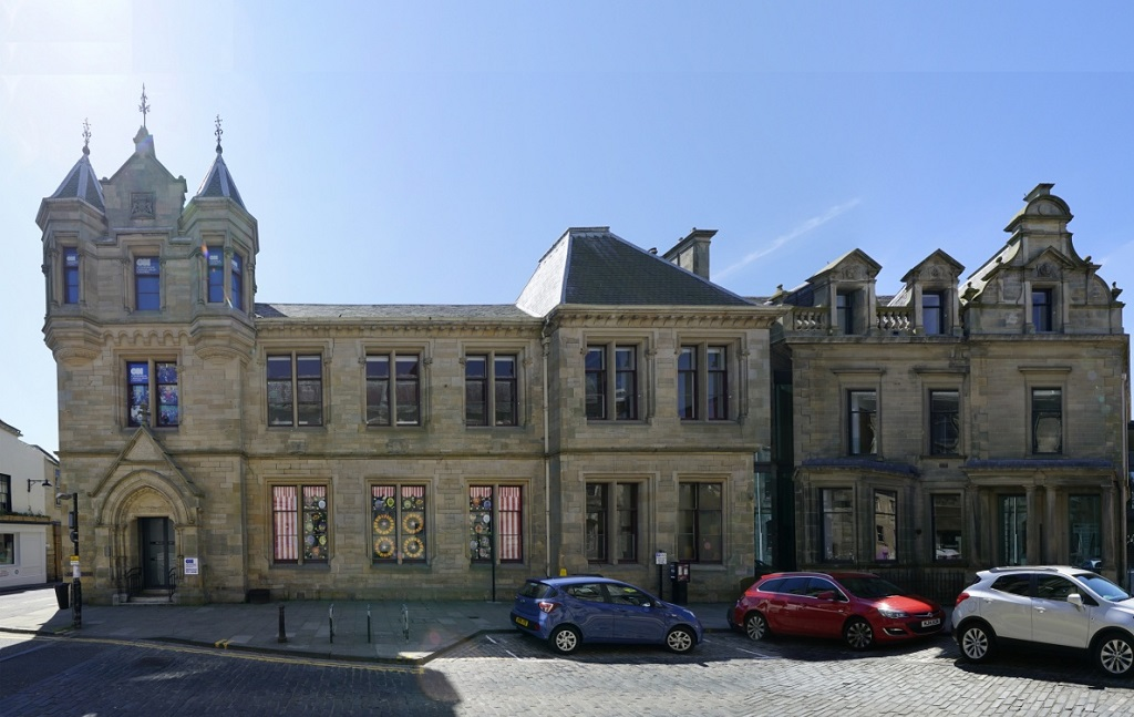 Cars parked in front of an ornate stone library building in a Scottish town centre. A small tower with turrets is above the main entrance to the building.