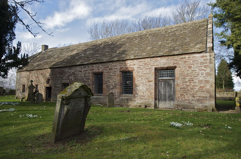 A modest stone chapel building surrounded by tombstones and snowdrops