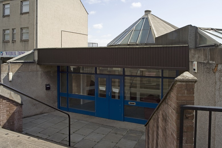 The entrance to a modern public library, slightly sunken below street level