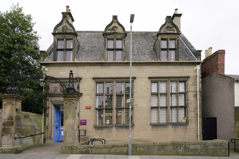 A small Carnegie library building accessed via a ornamental gateway made from stone and iron
